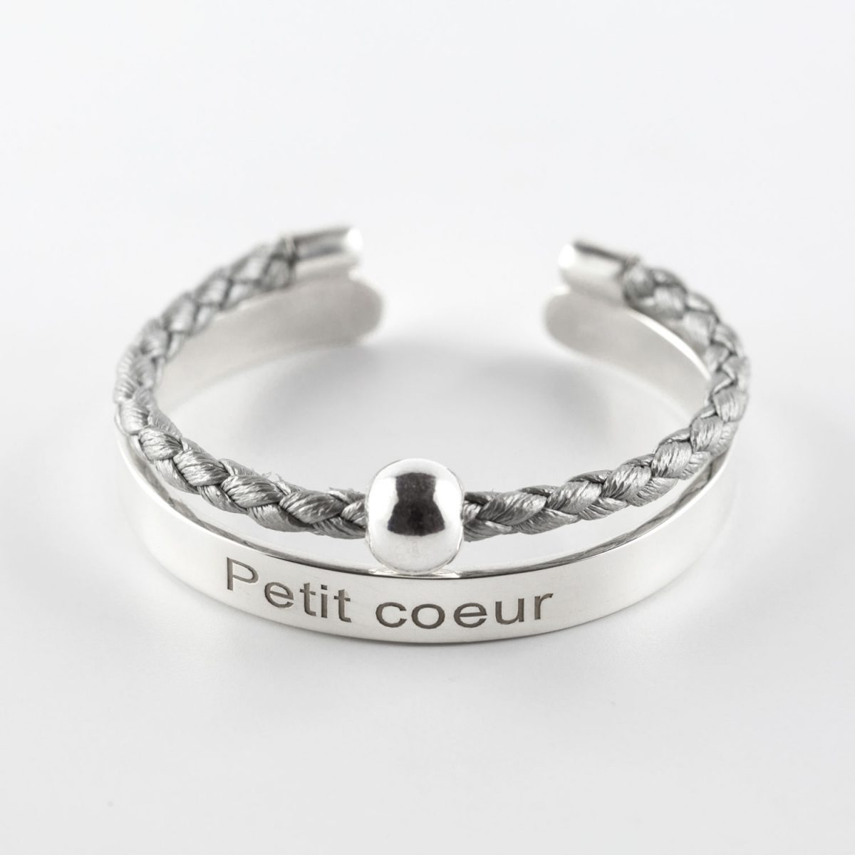 "Child's solid silver bangle with inscription ""Petit Coeur"" and silvery grey leather cord"