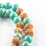 Child's Mâlâ necklace with turquoise beads and beige pompom